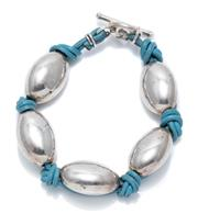 Sale 9012 - Lot 382 - A STERLING SILVER AND LEATHER BRACELET; 15.8 x 23.6mm oval hollow beads on plaited blue leather strap to toggle clasp, length 20cm,...