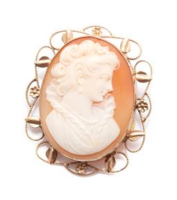 Sale 9253J - Lot 426 - A VINTAGE 9CT GOLD CAMEO BROOCH; featuring an oval carved shell cameo portrait of a lady to scrolling leaf and flower frame, with sa...