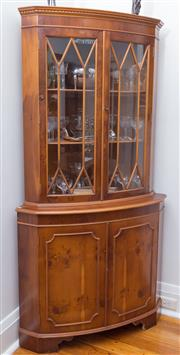 Sale 8530A - Lot 58 - A bow front yew wood corner cabinet. The dental carved top above 2 astragal glazed doors enclosing 2 shelves, the 2 lower figured pa...