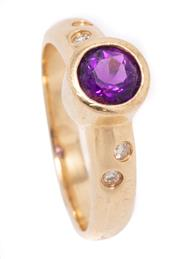 Sale 8999 - Lot 352 - A 14CT GOLD AMETHYST AND DIAMOND RING; rub set with a round cut amethyst to 8.2mm wide round shoulders gypsy set with 4 round brilli...