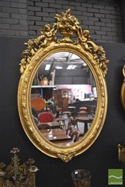 Sale 8255 - Lot 1029 - Late 19th Century French Gilt Gesso Oval Mirror, with beaded frame, surmounted by angels & an urn (re gilded / slight damage to top,...