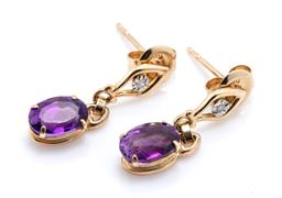 Sale 9221 - Lot 305 - A PAIR OF 10CT GOLD AMETHYST AND DIAMOND EARRINGS; each an oval cut deep purple amethyst drop to stud fitting illusion set with a si...