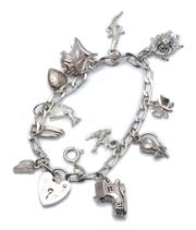 Sale 9029 - Lot 318 - A SILVER CHARM BRACELET; filed curb links to a heart shaped padlock clasp hallmarked ASJ London, 1985, attached with 12 charms, leng...