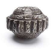Sale 8517A - Lot 83 - A hinged silver circular domed repousse tobacco box with radiating floral motif and ribbed edge, Sumbawa, 65g, D 10cm