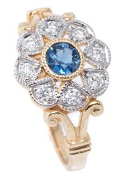 Sale 8982 - Lot 374 - AN EDWARDIAN STYLE SAPPHIRE AND DIAMOND CLUSTER RING; centring a round cut blue sapphire of approx. 0.39ct to surround of 8 round br...