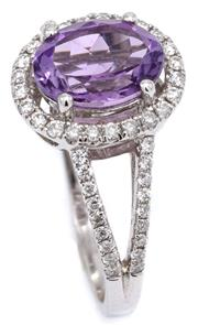 Sale 9090J - Lot 394 - AN 18CT WHITE GOLD AMETHYST AND DIAMOND RING; claw set with an approx. 1.70ct oval cut amethyst to a halo surround and split shoulde...