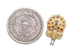 Sale 9246J - Lot 313 - TWO SILVER BROOCHES; a 58mm round Mexian silver Aztec sun calendar with concealed bale, rubbed hallmarks and Eagle 26, and a Thai en...