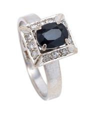 Sale 8991 - Lot 324 - A VINTAGE 14CT WHITE GOLD SAPPHIRE AND DIAMOND RING; centring an oval cut dark blue sapphire (chipped) to rectangular surround set w...