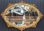 Sale 8287A - Lot 33 - A charming & unusual oval ornate gilt mirror with bevelled glass, 70cm high x 86cm wide