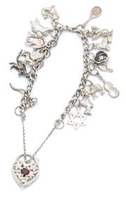 Sale 9046 - Lot 321 - A SILVER CHARM BRACELET; curb links to garnet set pierced heart shape padlock clasp and safety chain, attached with various charms,...