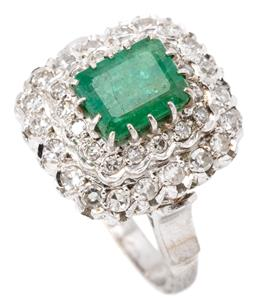 Sale 9149 - Lot 413 - A VINTAGE EMERALD AND DIAMOND COCKTAIL RING; set in 10ct white gold with an emerald cut emerald of approx. 1.70ct (surface reaching...
