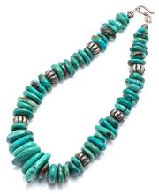 Sale 9083 - Lot 330 - A TRIBAL TURQUOISE BEAD NECKLACE; composed of 15 - 34mm flat tumbled beads spaced with reeded nickel silver beads to a scroll clasp,...