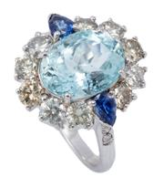 Sale 8999 - Lot 387 - AN AQUAMARINE DIAMOND AND SAPPHIRE CLUSTER RING; bead claw set in 18ct white gold with an oval cut aquamarine of approx. 3.3ct to su...