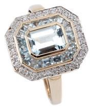 Sale 9046 - Lot 386 - A DECO STYLE AQUAMARINE AND DIAMOND RING; octagonal top centring an emerald cut aquamarine surrounded by mixed cut aquamarines to a...
