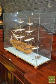 Sale 8267 - Lot 1085 - Wooden Model Ship of The Royal Caroline (launched 1749) in a glass case (crack to end pane) on a gilt rope edged base