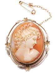 Sale 8965 - Lot 338 - A CARVED SHELL CAMEO BROOCH; featuring a female portrait set in a 9ct two tone gold floral frame, 40 x 32mm, with safety chain, wt....