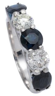 Sale 8965 - Lot 374 - A HALF HOOP SAPPHIRE AND DIAMOND RING; set in platinum with a round and 2 blue oval cut sapphires adjacent to 2 round brilliant cut...