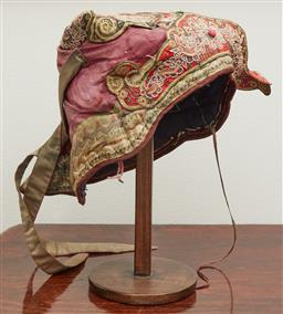 Sale 9108H - Lot 25 - A vintage Indonesian embroidered cap on a timber stand Height 30cm