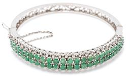 Sale 9149 - Lot 414 - AN EMERALD AND DIAMOND BANGLE; 12mm wide tapered hinged bangle set across the top with 50 graduated round cut emeralds to scalloped...
