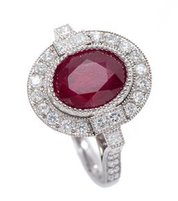 Sale 9213 - Lot 393 - AN 18CT WHITE GOLD RUBY AND DIAMOND DRESS RING; millegrain set with an oval cut treated ruby of approx. 4.80ct surrounded by 16 roun...