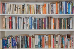 Sale 9108H - Lot 30 - A large quantity of paperback books over three shelves.
