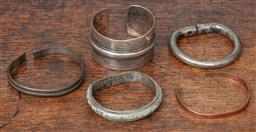Sale 9120H - Lot 73 - A collection of five cuff bangles including an African sterling silver example, possible Tunisian mark, two 600 silver examples and...