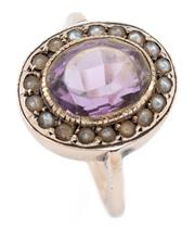 Sale 9054 - Lot 368 - A VINTAGE 9CT GOLD AMETHYST AND SEED PEARL RING; centring a 10.7 x  8.5mm amethyst (abraded) surrounded by seed pearls set into a la...