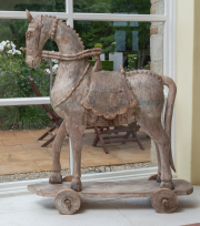 Sale 8677B - Lot 536 - A vintage distressed teak horse on cart, Height 118cm