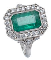 Sale 8965 - Lot 398 - AN EMERALD AND DIAMOND RING; millegrain set in platinum with an emerald cut emerald of approx. 3.25ct to surround and Prince of Wale...
