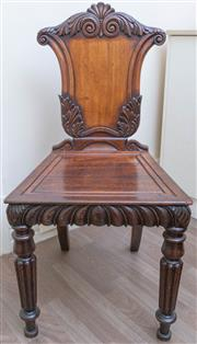 Sale 8800 - Lot 204 - A pair of early mahogany hall chairs with scrolled carved shield back, and carved and outswept legs