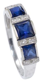 Sale 8965 - Lot 372 - A 9CT WHITE GOLD STONE SET RING; set with 3 French cut synthetic blue stones and 4 round brilliant cut diamonds, size R, wt. 2.7g.