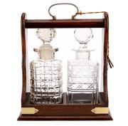 Sale 8697A - Lot 62 - An Edwardian timber tantalus, with plated hardware encasing two non-matching cut crystal decanters, with keys, H 31 x W 25cm