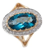 Sale 9046 - Lot 518 - A LONDON BLUE TOPAZ AND DIAMOND RING; oval top cut down claw set with a blue oval topaz surrounded by round brilliant cut diamonds i...