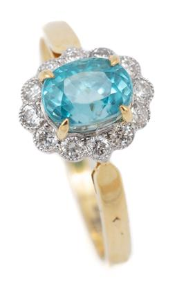 Sale 9164J - Lot 521 - AN 18CT GOLD ZIRCON AND DIAMOND CLUSTER RING; centring a blue oval cut zircon to a scalloped surround millegrain set with 12 round b...
