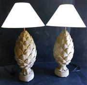 Sale 8272A - Lot 78 - A pair of large cast stone pineapple finials converted to table lamps Overall height to brass lamp holders 64 cm  plus shades