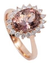 Sale 9054J - Lot 133 - A TANZANITE AND DIAMOND CLUSTER RING; set in 18ct rose gold with a central 3.18ct oval cut pinkish brown tanzanite (ziosite) to surr...