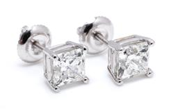 Sale 9253J - Lot 409 - A PAIR OF 14CT WHITE GOLD SOLITAIRE DIAMOND STUD EARRING; each set with a princess cut diamond, 1 = 1.01ct G/VS1 with GSL cert, 1 =...