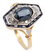 Sale 9074 - Lot 376 - AN 18CT GOLD LATE DECO SAPPHIRE AND DIAMOND RING; long octagonal top centring a dark blue oval cut sapphire of approx. 1.30ct surrou...