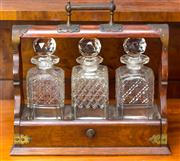 Sale 8342A - Lot 90 - An Edwardian timber tantalus, with brass hardware, encasing three cut crystal decanters, (one small chips to rim), with key, H 34 x...
