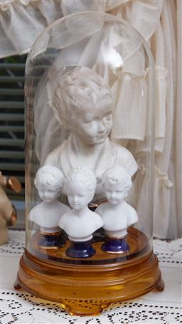 Sale 9103M - Lot 436 - A glass dome with four Limoges porcelain busts of children , tallest bust, Height 19cm