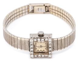 Sale 9132 - Lot 425 - A VINTAGE 18CT WHITE GOLD EBEL LADYS WRISTWATCH; square dial with applied markers, bezel set with 16 round brilliant cut and 4 squa...