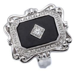 Sale 9164J - Lot 455 - AN EDWARDIAN STYLE DIAMOND AND ONYX RING; emerald shape mount with scroll surround set with an onyx plaque inset with a round brilli...