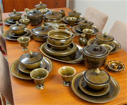 Sale 9164H - Lot 17 - A large olive green celadon glazed dinner service individually hand crafted including tureens, footed cups, gravy boat, dinner plate...