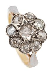 Sale 9066 - Lot 382 - A VINTAGE 18CT GOLD DIAMOND DAISY CLUSTER RING; center set with an Old European cut diamond of approx. 0.24ct (nick on table), surro...
