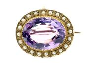 Sale 8357 - Lot 334 - AN ANTIQUE 9CT GOLD GEMSET BROOCH; cut down claw set with an oval amethyst estimated as 14.00ct to a border of half pearls.