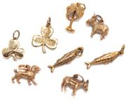 Sale 9046 - Lot 312 - A GROUP OF GOLD CHARMS; 2 x 15ct shamrocks, wt. 3.02g, a 12ct dog, wt. 0.76ct, 2 fish and 2 donkeys in 9ct, wt. 8.25g, and a gold pl...