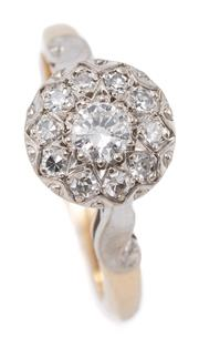 Sale 9066 - Lot 384 - A VINTAGE GOLD DIAMOND CLUSTER RING; illusion setting in palladium centring a round brilliant cut diamond of approx. 0.17ct (nick on...
