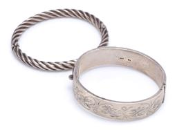Sale 9194 - Lot 320 - TWO STERLING SILVER HINGED BANGLES; 6.3mm wide hinged hollow twist, internal diam. 62.3 x 54.8mm, other 16mm wide hollow hinged bang...