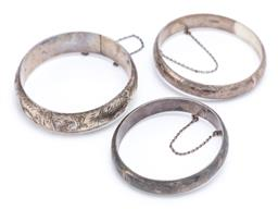 Sale 9194 - Lot 566 - THREE SIAM STERLING SILVER BANGLES; 10.6-16mm wide all half round hollow hinged bangles with engraved scrolling motifs to box clasps...