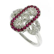 Sale 8347J - Lot 406 - A DECO STYLE DIAMOND AND RUBY RING; centring 3 round brilliant cut diamonds to a surround of small rubies between shoulders each set...